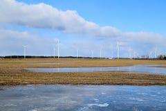 Πάρκο ανεμόμυλων στη Λετονία - άποψη από ploughland με τα παγωμένα νερά Στοκ Φωτογραφία
