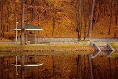 Πάρκο με την πέργκολα στο φθινόπωρο πτώσης και την αντανάκλαση λιμνών Στοκ Εικόνες