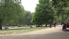 Πάρκο του Λονδίνου James, χαλάρωση τουριστών ανθρώπων που στηρίζεται στη χλόη στο πικ-νίκ φιλμ μικρού μήκους