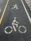 Πάροδος πατινάζ κυλίνδρων στις κίτρινων και άσπρων διαχωριστικές γραμμές πορειών ποδηλάτων, με τους δείκτες για τους σκέιτερ και  στοκ εικόνες