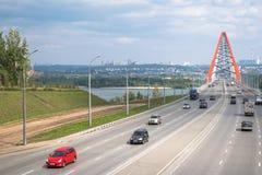Πάροδοι με τα αυτοκίνητα και την κόκκινη γέφυρα στοκ εικόνα