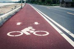 Πάροδος ποδηλάτων ή πορεία, σύμβολο εικονιδίων στον κόκκινο δρόμο ασφάλτου Στοκ φωτογραφία με δικαίωμα ελεύθερης χρήσης