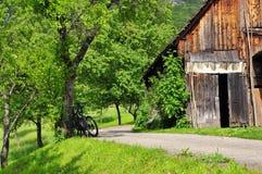 Πάροδος ποδηλάτων βουνών και παραδοσιακή ξύλινη καλύβα σανού Στοκ Εικόνες