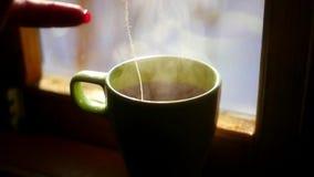 Πάρτε ένα φλυτζάνι του ζεστού νερού με την τσάντα τσαγιού Α κόκκινη, πέρα δώθε, για να παρασκευάσετε ένα εύγευστο τσάι, ενάντια σ φιλμ μικρού μήκους