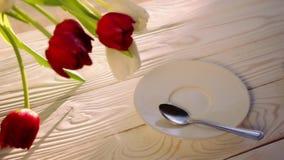 Πάρτε και βάλτε ένα φλιτζάνι του καφέ με ένα σχέδιο τέχνης latte σε έναν άσπρο ξύλινο πίνακα με μια ανθοδέσμη των τουλιπών απόθεμα βίντεο