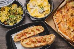 Πάρτε μαζί τα ιταλικά τρόφιμα ζυμαρικών Πίτσα με τα πράσινα πιπέρια κιβωτίων, το ψωμί σκόρδου, το fetuccine και ravioli στο πλαστ στοκ φωτογραφία
