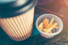 Πάρτε μαζί το καυτά φλυτζάνι και το πρόχειρο φαγητό κατανάλωσης καφέ εγγράφου στο ξύλινο tabl Στοκ Φωτογραφίες