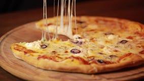 Πάρτε μια φέτα πιτσών από τον ξύλινο πίνακα φιλμ μικρού μήκους