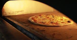 Πάρτε τη μαγειρεύοντας πίτσα από έναν καυτό φούρνο απόθεμα βίντεο