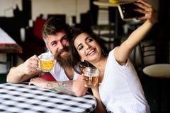 Πάρτε selfie τη φωτογραφία για να θυμηθείτε τη μεγάλη ημερομηνία στο μπαρ Το ζεύγος ερωτευμένο κατά την ημερομηνία πίνει την μπύρ στοκ φωτογραφία με δικαίωμα ελεύθερης χρήσης