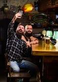 Πάρτε selfie τη φωτογραφία για να θυμηθείτε το μεγάλο βράδυ στο μπαρ Σε απευθείας σύνδεση επικοινωνία Γενειοφόρο smartphone λαβής στοκ εικόνα με δικαίωμα ελεύθερης χρήσης