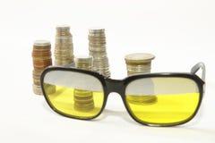 Πάσσαλοι των νομισμάτων και των παλαιών γυαλιών ηλίου ύφους στοκ φωτογραφία με δικαίωμα ελεύθερης χρήσης