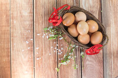 Πάσχα - αυγά κοτών σε ένα ψάθινο καλάθι με ένα ΛΦ κορδελλών και ανοίξεων Στοκ φωτογραφία με δικαίωμα ελεύθερης χρήσης
