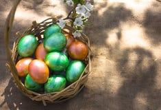 Πάσχα ευτυχές Ζωηρόχρωμα αυγά Πάσχας στα ψάθινα καλάθια, σε υπαίθριο Ανασκόπηση Πάσχας με το copyspace Στοκ Φωτογραφίες