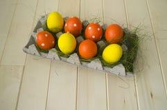 Πάσχα Τα αυγά Πάσχας είναι κίτρινα και πορτοκαλιά Τα αυγά βρίσκονται στο εμπορευματοκιβώτιο για τα αυγά Πράσινη χλόη Στοκ φωτογραφίες με δικαίωμα ελεύθερης χρήσης