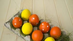 Πάσχα Τα αυγά Πάσχας είναι κίτρινα και πορτοκαλιά Τα αυγά βρίσκονται στο εμπορευματοκιβώτιο για τα αυγά Πράσινη χλόη Στοκ φωτογραφία με δικαίωμα ελεύθερης χρήσης