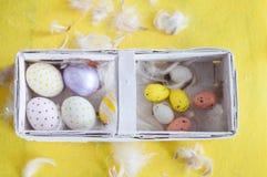 Πάσχα, χρωματισμένα αυγά, κίτρινος, άσπρα, σε ένα καλάθι, καλάθι feathersa των αυγών, αυγά κοτόπουλου, αυγά ορτυκιών, Στοκ φωτογραφία με δικαίωμα ελεύθερης χρήσης