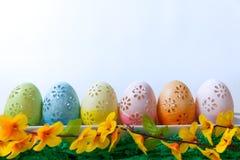 Πάσχα, χρωματισμένα αυγά Πάσχας που τίθενται σε μια διακόσμηση Πάσχας κύπελλων πίσω από ένα άσπρο υπόβαθρο Στοκ φωτογραφία με δικαίωμα ελεύθερης χρήσης