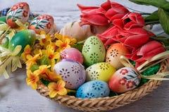 Πάσχα, χρωματισμένα αυγά Πάσχας που τίθενται σε μια διακόσμηση Πάσχας κύπελλων πίσω από ένα άσπρο υπόβαθρο Στοκ Φωτογραφίες