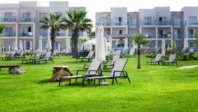 Πάφος, Κύπρος - 20 Ιουλίου 2017: Palm Beach με τα κενά sunbeds ενάντια στο ξενοδοχείο & Suitel αμφορέων Σύνολο στο ειδυλλιακό loc Στοκ εικόνα με δικαίωμα ελεύθερης χρήσης