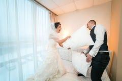 Πάλη μαξιλαριών της νύφης και του νεόνυμφου σε ένα δωμάτιο ξενοδοχείου Στοκ Εικόνες
