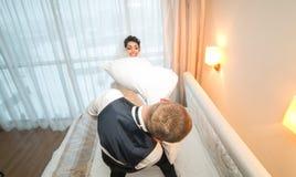 Πάλη μαξιλαριών της νύφης και του νεόνυμφου σε ένα δωμάτιο ξενοδοχείου Στοκ φωτογραφία με δικαίωμα ελεύθερης χρήσης
