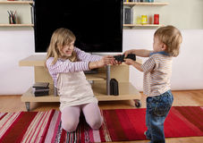 Πάλη μικρών παιδιών με την αδελφή του πέρα από τον τηλεχειρισμό Στοκ Εικόνες