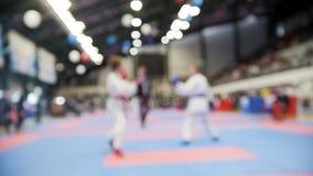 Πάλη karatekas παιδιών karate στους ανταγωνισμούς, σε αργή κίνηση de-στραμμένο αθλητικό υπόβαθρο φιλμ μικρού μήκους