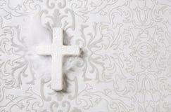 Πένθος: άσπρος κεραμικός σταυρός στο γκρίζο υπόβαθρο διακοσμήσεων στοκ φωτογραφίες