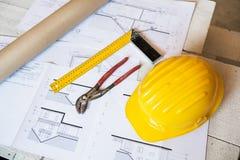 Πένσες, τετράγωνο, κράνος και σχεδιαγράμματα στο εργοτάξιο οικοδομής Στοκ Εικόνα