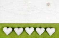 Πέντε άσπρες καρδιές στο ξύλινο άσπρο shabby κομψό υπόβαθρο με το AP Στοκ εικόνα με δικαίωμα ελεύθερης χρήσης