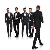 Πέντε άτομα έντυσαν στα tuxedoes με το περπάτημα ηγετών πίσω στοκ εικόνα