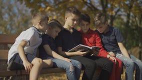 Πέντε αγόρια που κάθονται στον πάγκο και που οδηγούν ένα περιοδικό Οι φίλοι ξοδεύουν το χρόνο στη μεγάλη επιχείρηση σε μια ηλιόλο φιλμ μικρού μήκους