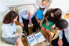Πέντε επιχειρηματίες στη συνεδρίαση των ομάδων που μελετά τις γραφικές παραστάσεις Στοκ Φωτογραφία