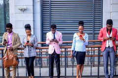 Πέντε εργαζόμενοι γραφείων που στέκονται με τα τηλέφωνα mobiles και που δακτυλογραφούν sms ο ένας στον άλλο στοκ φωτογραφία