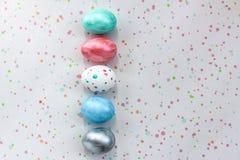 Πέντε ζωηρόχρωμα αυγά βρίσκονται σε ένα επισημασμένο υπόβαθρο Πάσχα, δημιουργικά χρωματίζοντας αυγά ανεξάρτητα στο σπίτι για τη δ στοκ φωτογραφία με δικαίωμα ελεύθερης χρήσης