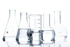 Πέντε κλασικές εργαστηριακές φιάλες με ένα σαφές υγρό στοκ εικόνα