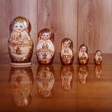 Πέντε κούκλες σε έναν καφετή ξύλινο πίνακα και μια σύσταση στο υπόβαθρο στοκ εικόνες
