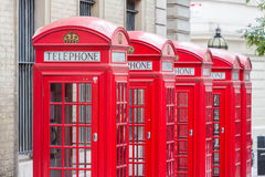 Πέντε κόκκινα τηλεφωνικά κιβώτια του Λονδίνου όλα σε μια σειρά Στοκ Φωτογραφία