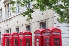 Πέντε κόκκινα τηλεφωνικά κιβώτια του Λονδίνου όλα σε μια σειρά Στοκ Εικόνες