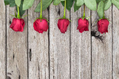 Πέντε κόκκινα τριαντάφυλλα στο ξύλινο υπόβαθρο, τοπ άποψη Στοκ εικόνα με δικαίωμα ελεύθερης χρήσης