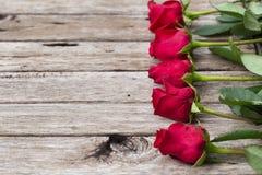 Πέντε κόκκινα τριαντάφυλλα στο ξύλινο υπόβαθρο Στοκ εικόνες με δικαίωμα ελεύθερης χρήσης