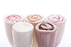 Πέντε ποτήρια της διάφορης σοκολάτας, της φράουλας και της βανίλιας milkshakes που απομονώνονται στο άσπρο υπόβαθρο στοκ εικόνα με δικαίωμα ελεύθερης χρήσης
