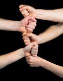 Πέντε πυγμές που συσσωρεύονται ο ένας στον άλλο σε ένα μαύρο υπόβαθρο Στοκ εικόνα με δικαίωμα ελεύθερης χρήσης