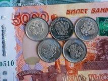 Πέντε ρωσικά νομίσματα βρίσκονται σε ένα τραπεζογραμμάτιο πέντε χιλιάες ρουβλιών Στοκ φωτογραφίες με δικαίωμα ελεύθερης χρήσης