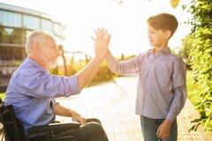 πέντε υψηλά Ο ηληκιωμένος σε μια αναπηρική καρέκλα χαιρετά τον εγγονό του Στοκ φωτογραφία με δικαίωμα ελεύθερης χρήσης