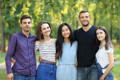 Πέντε φίλοι γυναικών και ανδρών στο πράσινο δασικό υπόβαθρο Στοκ εικόνα με δικαίωμα ελεύθερης χρήσης