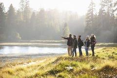 Πέντε φίλοι που περπατούν κοντά σε μια λίμνη παίρνουν κατά την άποψη, κάποιος δείχνει Στοκ Φωτογραφία