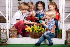 Πέντε χαριτωμένα μωρά κάθονται στο κατώφλι και παίρνουν έξω τα ζωηρόχρωμα αυγά από το καλάθι Πάσχα στοκ φωτογραφία