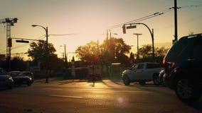 Πέρασμα αυτοκινήτων στο δραματικό φωτισμό ηλιοβασιλέματος απόθεμα βίντεο